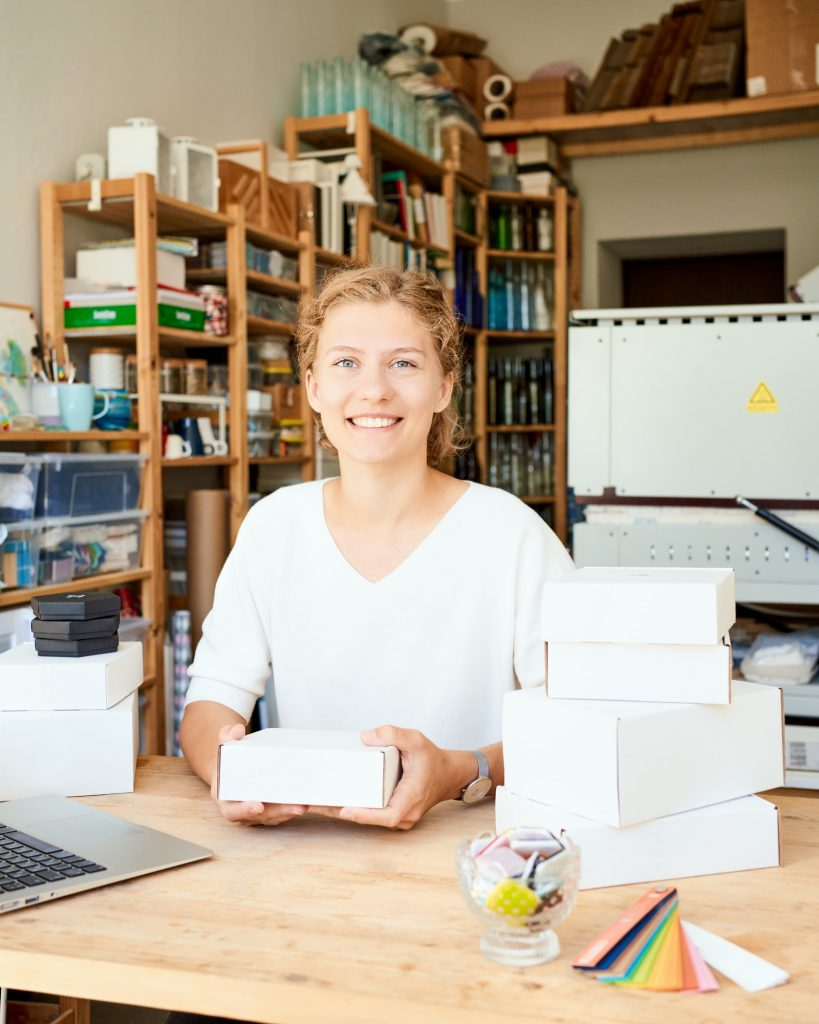 Happy owner of local business. Female entrepreneur collecting and packing gifts