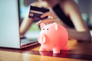 Pink,Color,Pig,Save,Bank,With,Woman,Holding,Credit,Card